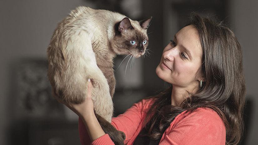 Frau hält Katze hoch