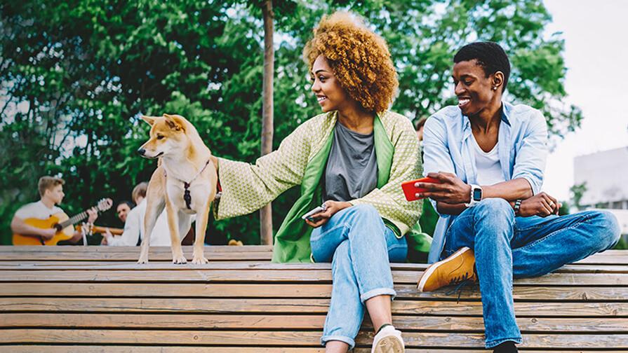Paar sitzt auf einer Bank mit ihrem Hund