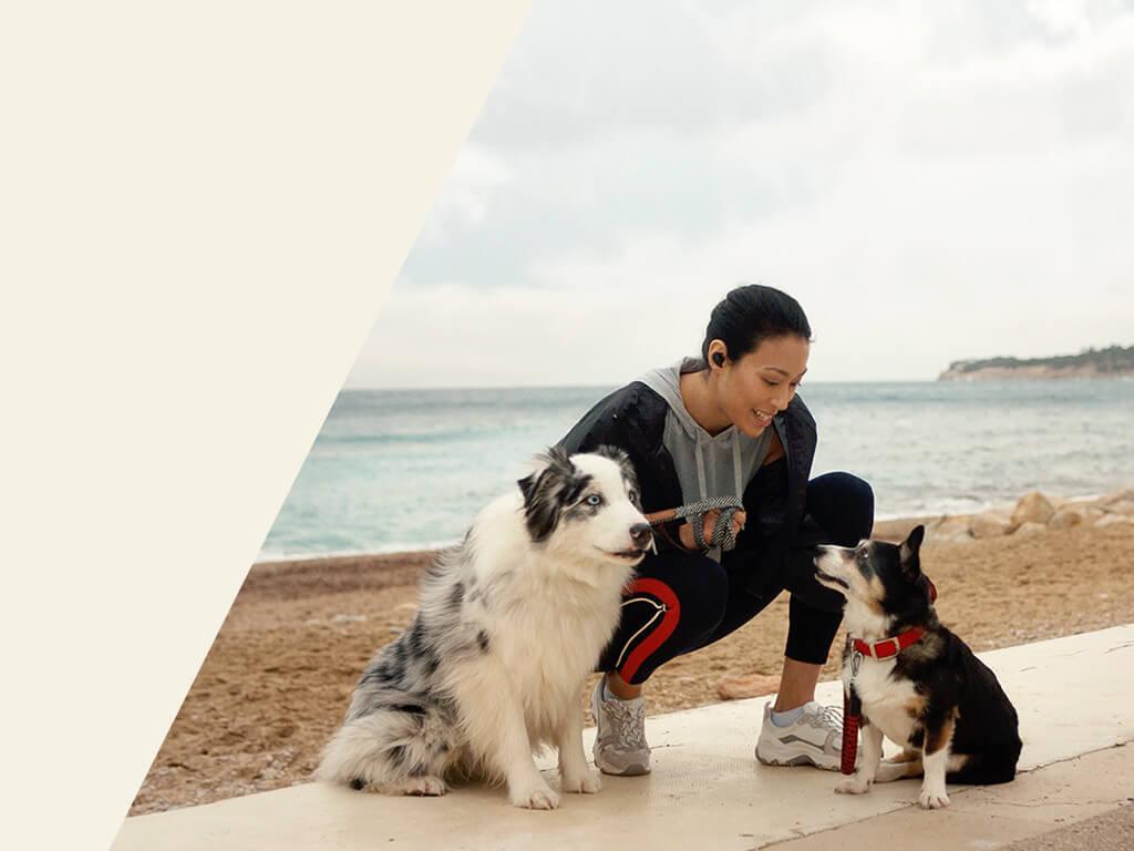 Frau mit zwei Hunden am Strand