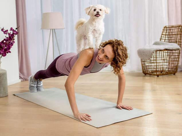 Beneful Frau macht Liegestütze mit Hund auf dem Rücken